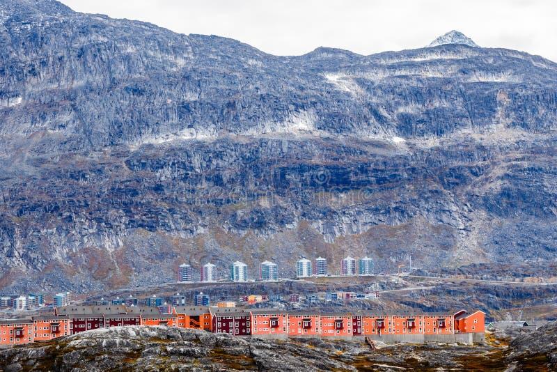 Rijen van kleurrijke moderne Inuit-huizen onder bemoste stenen met grijze steile hellingen van Weinig Malene-berg op de achtergro stock foto