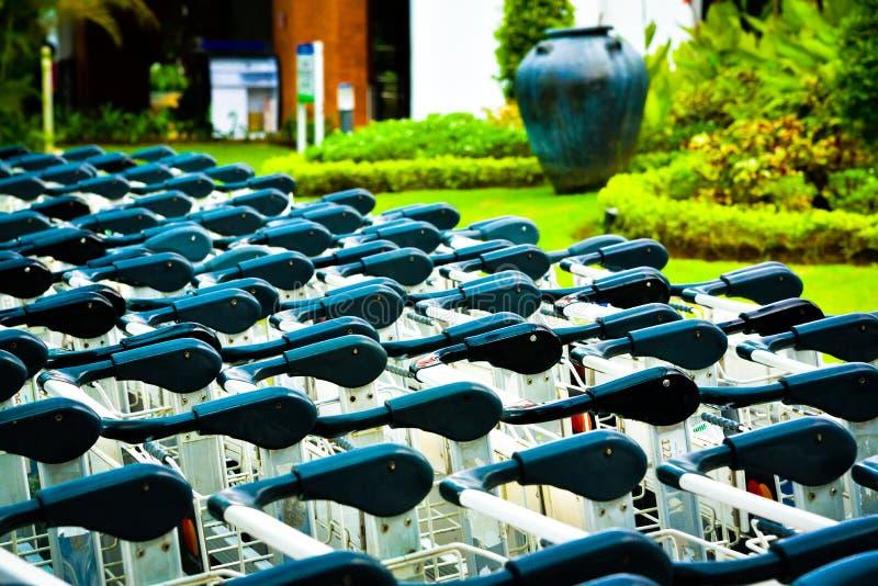 Rijen van lugagekarretjes bij de van het luchthavenaankomst en vertrek zitkamerpoort stock foto