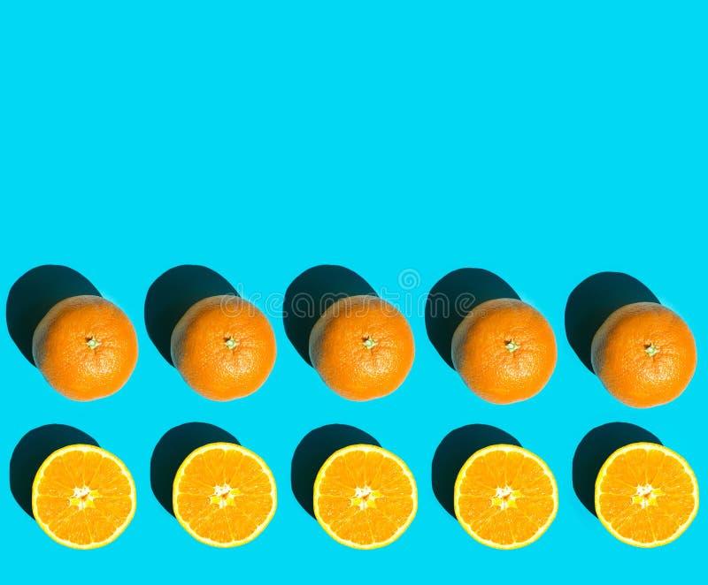 Rijen van rijpe sappige gehele en gehalveerde sinaasappel op blauwe achtergrond in helder ruw zonlicht met lange schaduw Gezonde  stock foto's