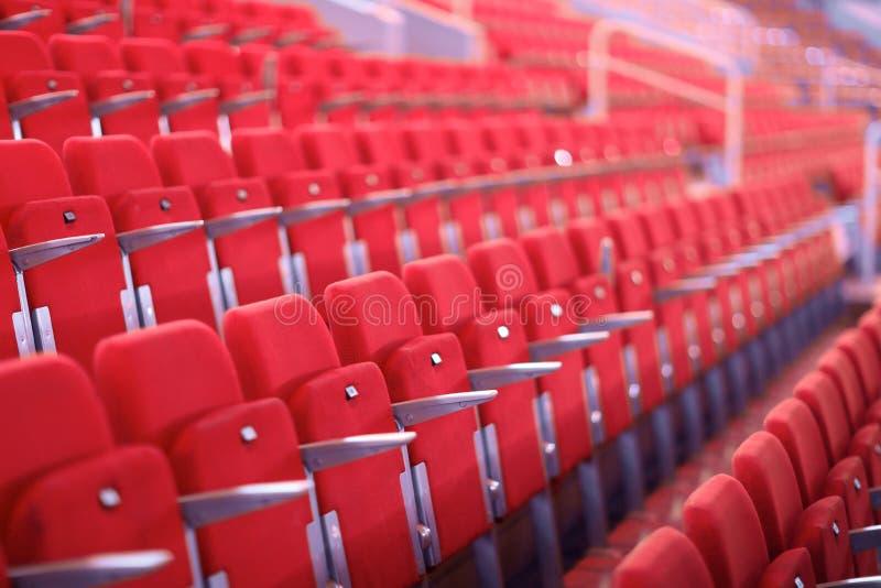 Rijen van rode genummerde zetels met armsteunen royalty-vrije stock fotografie