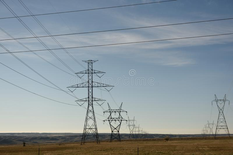 Rijen van torens van het metaal de de elektronet en lijnen van de hoogspanningsmacht met een blauwe hemel en een leeg landelijk l stock foto's