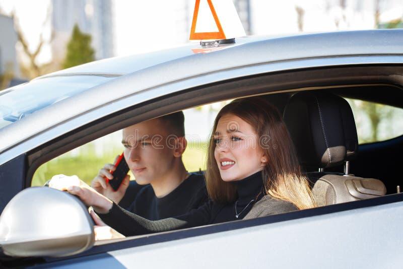 Rijinstructeur en vrouwelijke student in examenauto royalty-vrije stock afbeelding