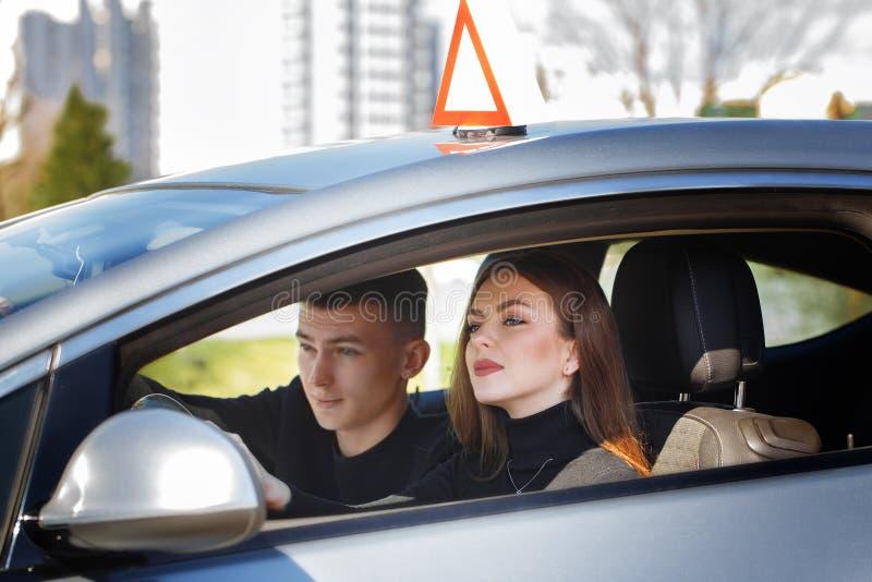 Rijinstructeur en vrouwelijke student in examenauto stock fotografie