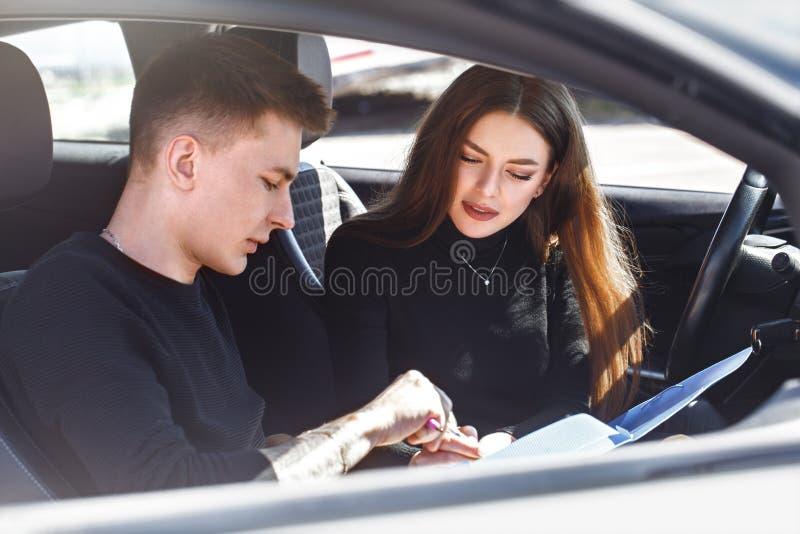 Rijinstructeur en vrouwelijke student in examenauto stock afbeeldingen