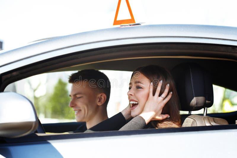 Rijinstructeur en vrouwelijke student in examenauto stock foto