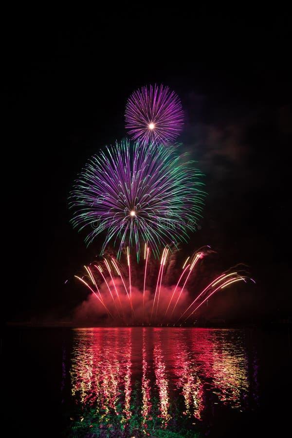 Rijk en kleurrijk vuurwerk over oppervlakte van Brno Dam met bezinning over de oppervlakte van meer stock foto's