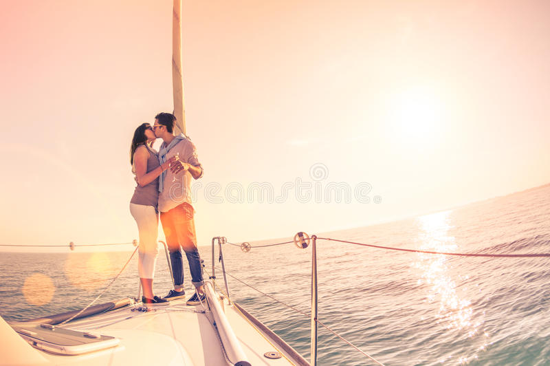 Rijk jong paar die in liefde op zeilboot bij zonsondergang toejuichen royalty-vrije stock foto's