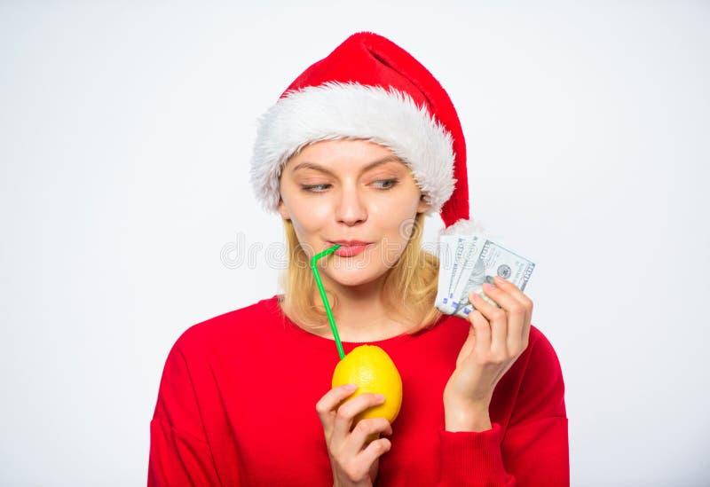 Rijk meisje met citroen en geld Het concept van het citroengeld De hoed van meisjessanta drinkt sapcitroen terwijl het geld van d royalty-vrije stock afbeeldingen