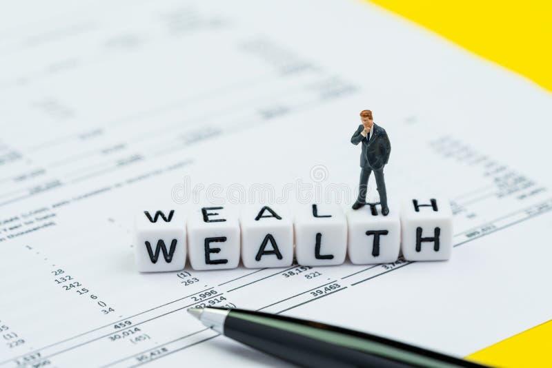 Rijkdombeheer, succesinvestering of financieel onafhankelijk concept, miniatuurzakenman die en zich op kubusblok bevinden denken royalty-vrije stock foto