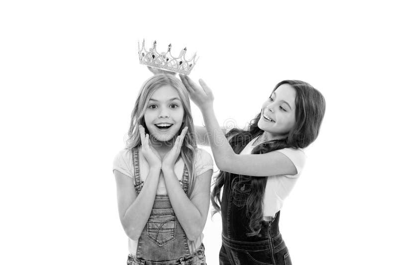 Rijke beloning Meisje dat kroon op hoofd van kleine schoonheidskoninginwinnaar zet als beloning Het aanbiddelijke minispectakel v royalty-vrije stock fotografie