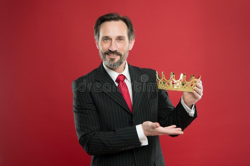 Rijke beloning Rijpe zakenman die kroonbeloning op rode achtergrond tonen Successfil grote chef- toekennende winnaar met stock afbeelding
