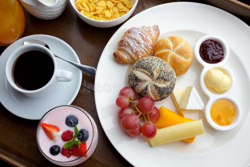 Rijke continentale ontbijt Franse knapperige croissants, muesli, veel zoete vruchten en bessen, hete koffie voor ochtend stock afbeelding