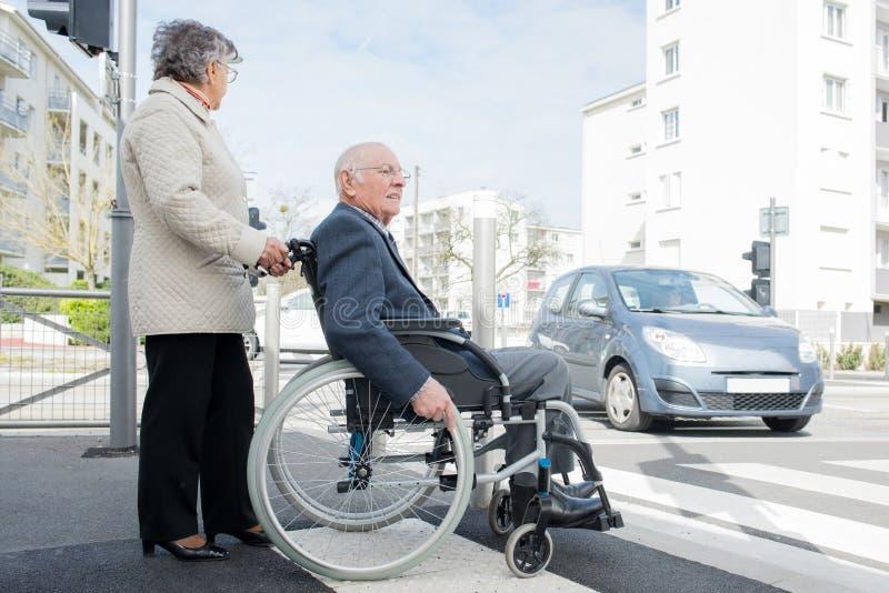 Rijke hogere mens in rolstoel met vrouwenpensionering royalty-vrije stock foto