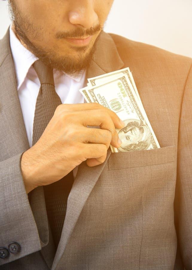 Rijke knap Close-up van de jonge mens in het zetten van geld in zijn zak royalty-vrije stock foto