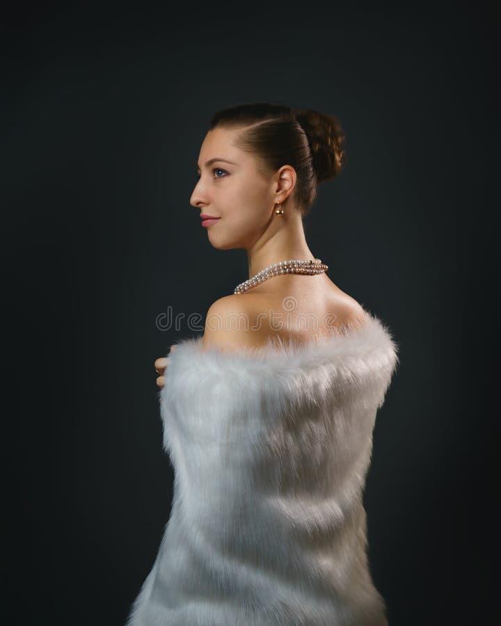 Rijke levensstijl Mooie seksuele vrouw die juwelen en de witte Schoonheid van het bontvest, manier dragen stock afbeelding