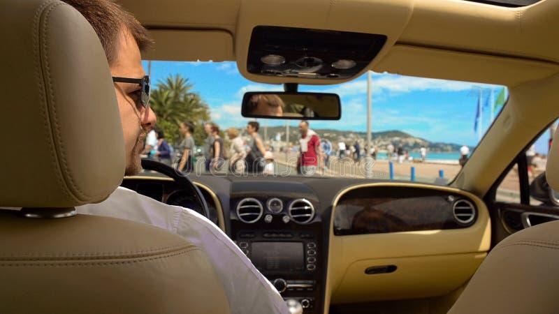 Rijke man die in zonnebril op groen licht wachten terwijl het zitten in dure auto stock foto