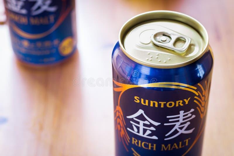 Rijke mout van het Suntory kan het Japanse bier in een blauw stock foto's