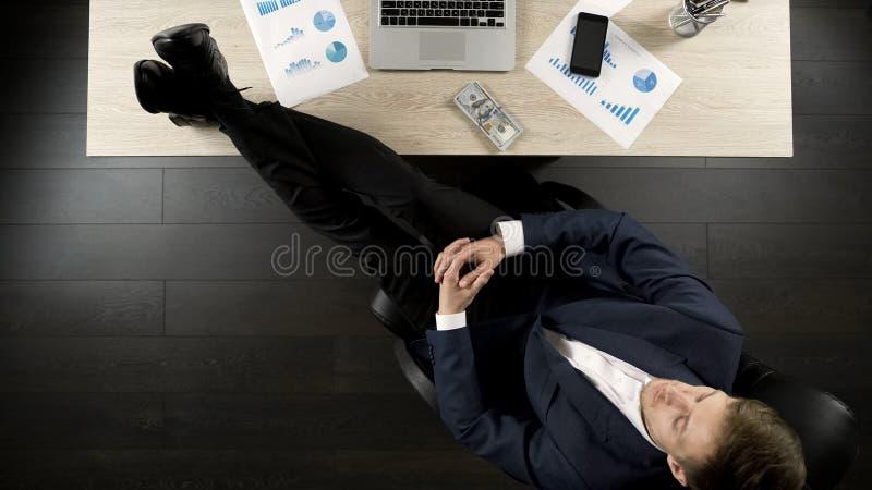 Rijke zakenman die van succes genieten, die met voeten op lijst, winnaar zitten stock foto