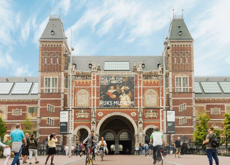 Rijksmuseum-Gebäudefassade mit Touristen und Radfahrern in Amsterdam lizenzfreies stockfoto