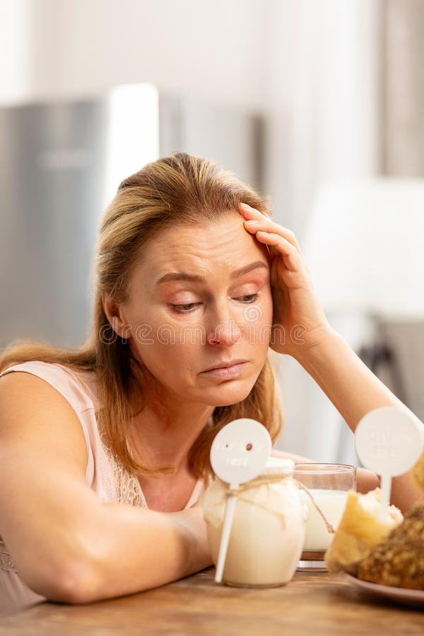 Rijp aantrekkelijk die vrouwengevoel van sterke voedselallergieën wordt vermoeid stock afbeelding