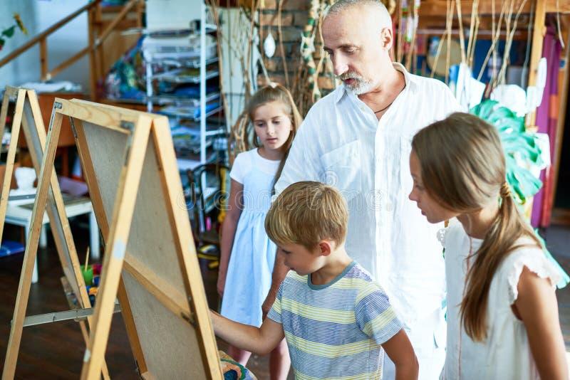 Rijp Art Teacher Working met Jonge geitjes royalty-vrije stock afbeelding