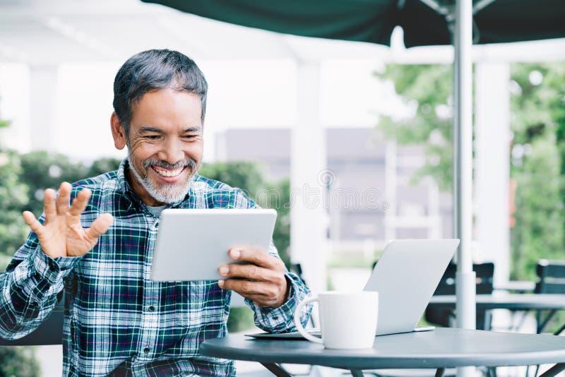 Rijp Aziatische mensen golvende hand met het glimlachen en geniet van gebruikend tablet makend tot videovraag aan kind, kleinkind stock foto