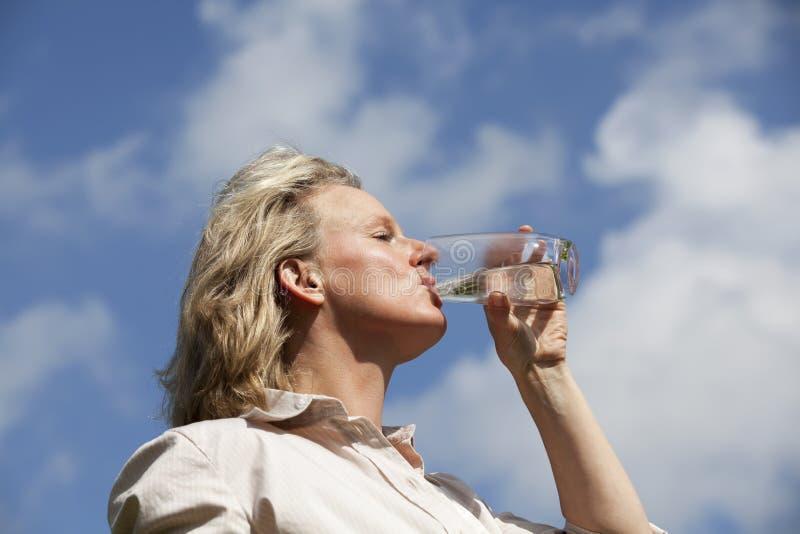 Rijp blond vrouwen drinkwater royalty-vrije stock afbeeldingen