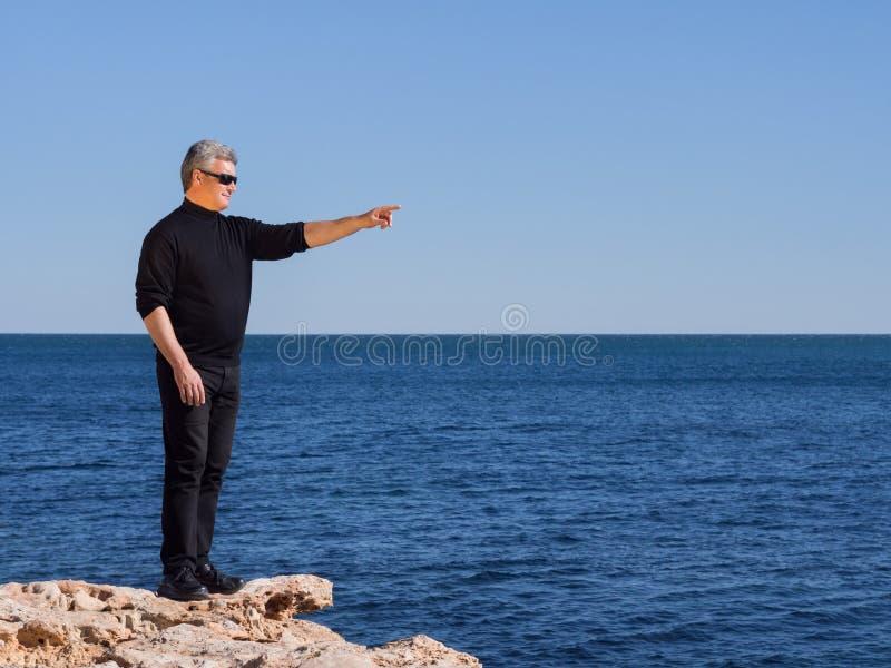 Rijp de midden-leeftijdsmens die zich op rots het richten bevinden stock afbeeldingen
