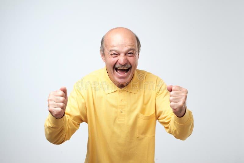 Rijp de Spaanse mens in gele overhemd het vieren overwinning van zijn team over grijze achtergrond stock foto