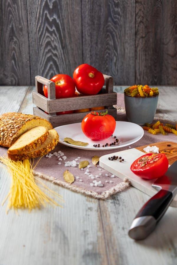 Rijp en heerlijk tomaten en tomatesap op een houten lijstachtergrond met één of andere deegwaren, basilicum, zout en peper stock foto's
