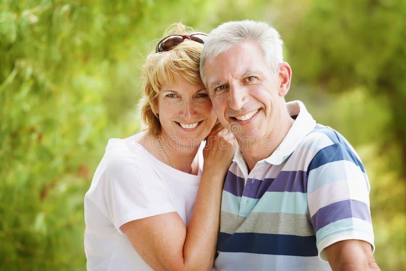Rijp en paar dat glimlacht omhelst royalty-vrije stock afbeeldingen
