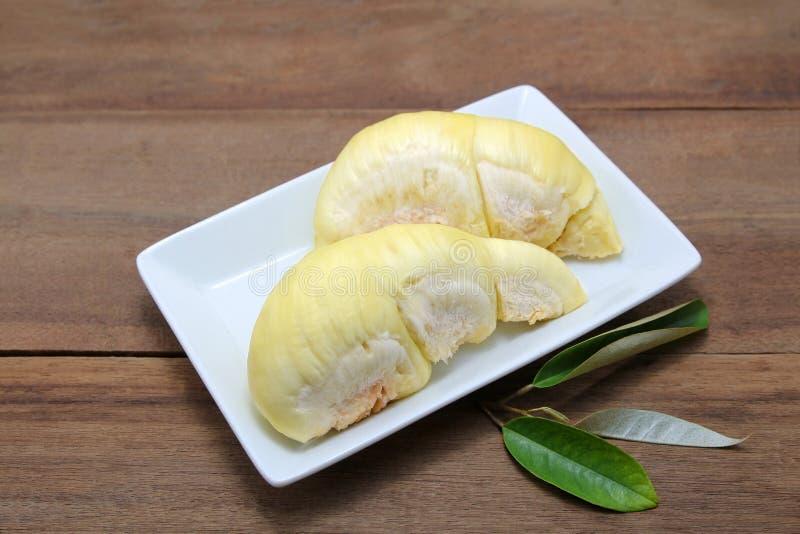 Rijp geel vlees van Durian op witte plaat, houten achtergrond royalty-vrije stock afbeeldingen