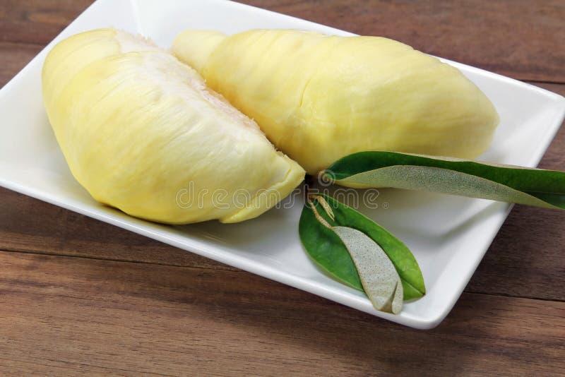 Rijp geel vlees van Durian op witte plaat, houten achtergrond royalty-vrije stock foto's