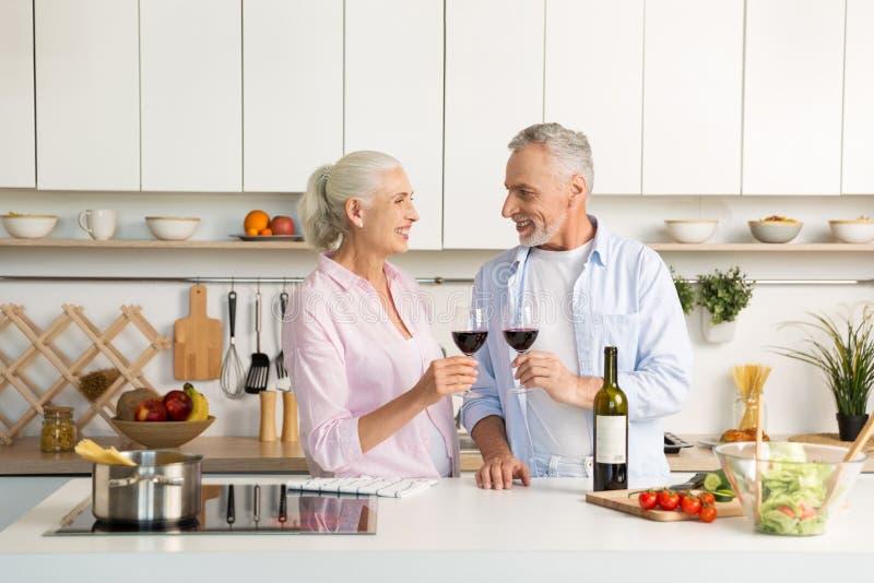 Rijp gelukkig houdend van paar die zich bij de keuken het drinken wijn bevinden stock foto