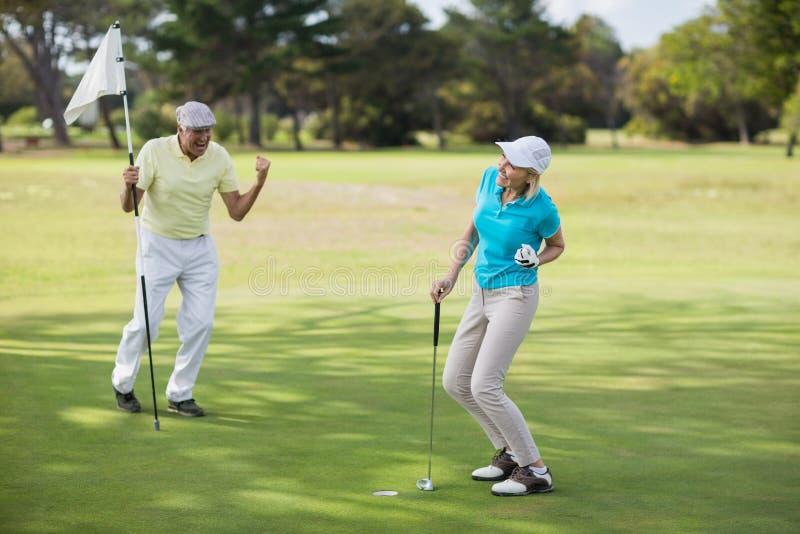 Rijp golfspelerpaar het vieren succes stock foto's