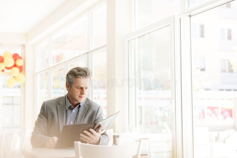 Rijp het menu van de klantenlezing terwijl het zitten bij lijst door venster in restaurant stock foto's