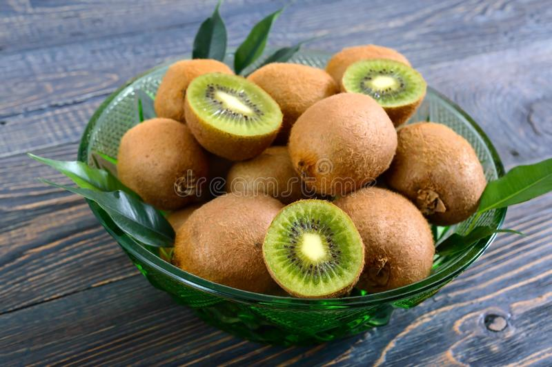 Rijp kiwifruit in een groene kom op een houten lijst royalty-vrije stock fotografie