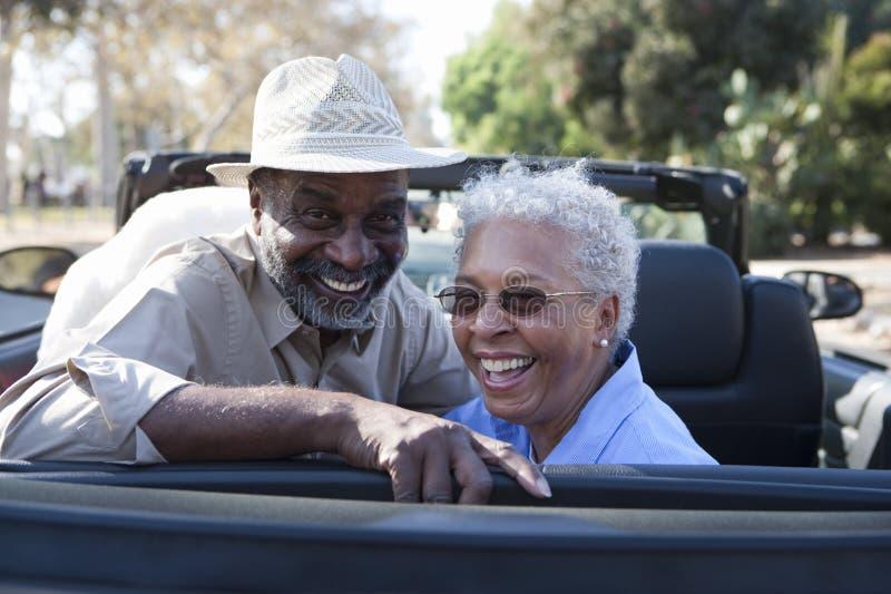 Rijp paar bij de achterbank van auto het glimlachen royalty-vrije stock afbeeldingen