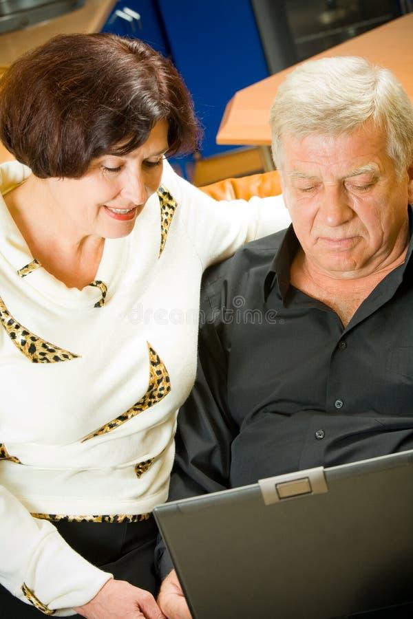 Rijp paar dat aan laptop werkt royalty-vrije stock afbeelding