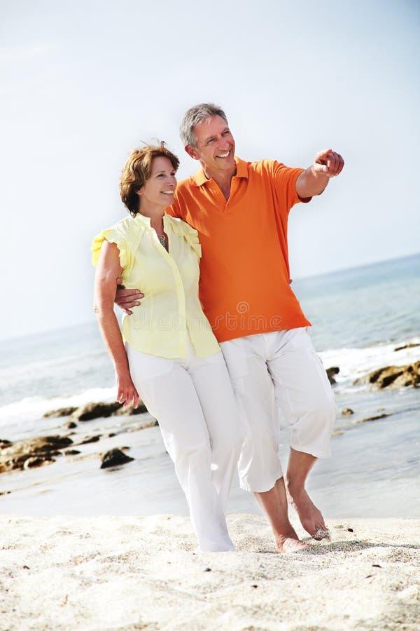 Rijp paar dat langs het strand loopt. royalty-vrije stock afbeelding