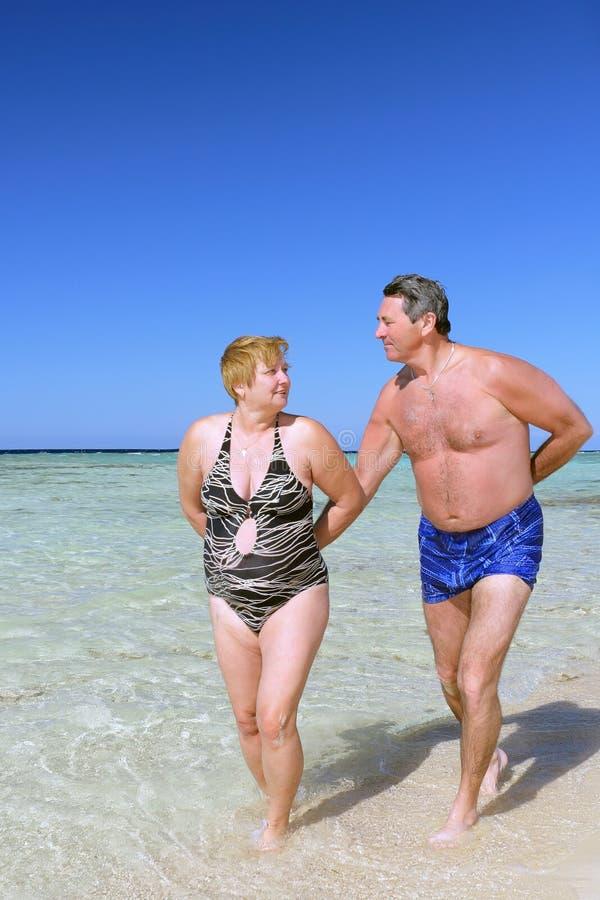 Rijp paar dat op het strand loopt. royalty-vrije stock afbeeldingen