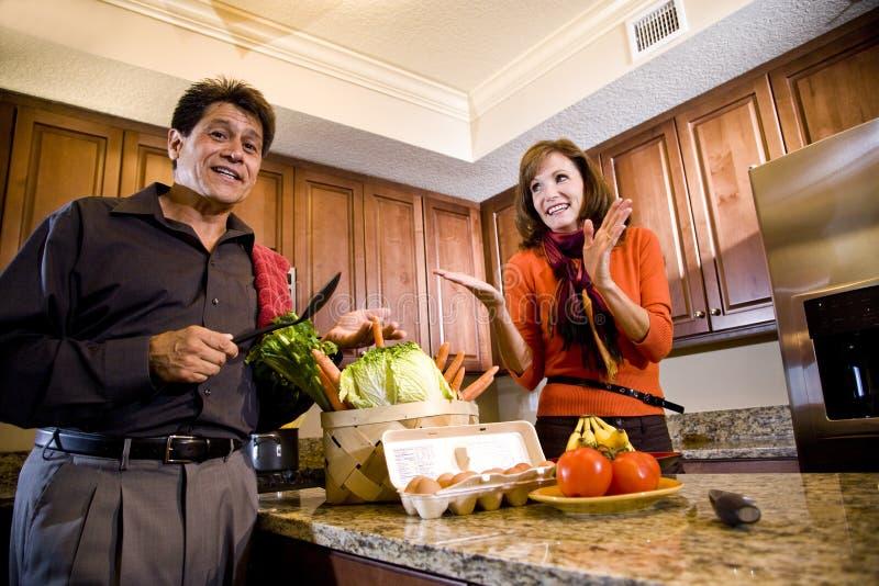 Rijp paar dat pret het koken in keuken heeft stock afbeelding