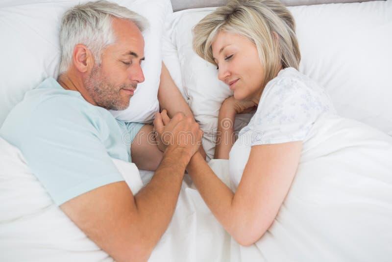 Rijp paar die in bed thuis liggen royalty-vrije stock foto