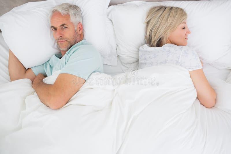 Rijp paar die in bed thuis liggen stock afbeeldingen