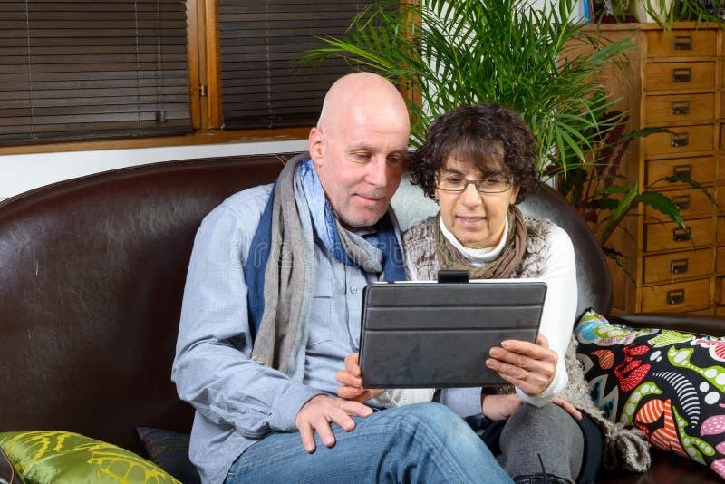 Rijp paar die een digitale tablet bekijken royalty-vrije stock afbeelding
