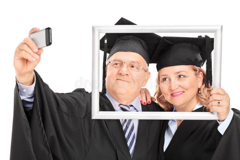 Rijp paar die een selfie nemen achter omlijsting stock foto