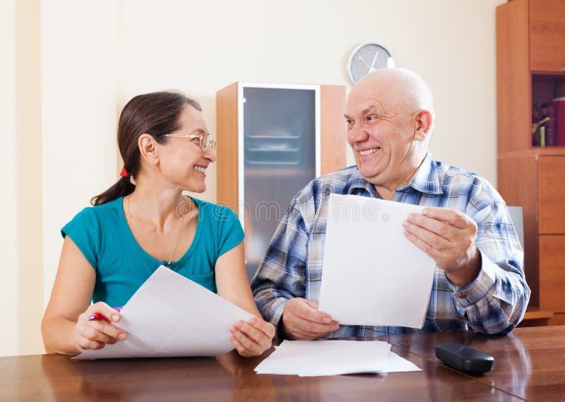 Rijp paar die financiële documenten houden stock afbeelding