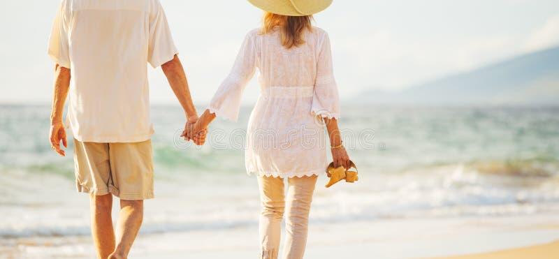 Rijp Paar die op het Strand bij Zonsondergang lopen royalty-vrije stock foto