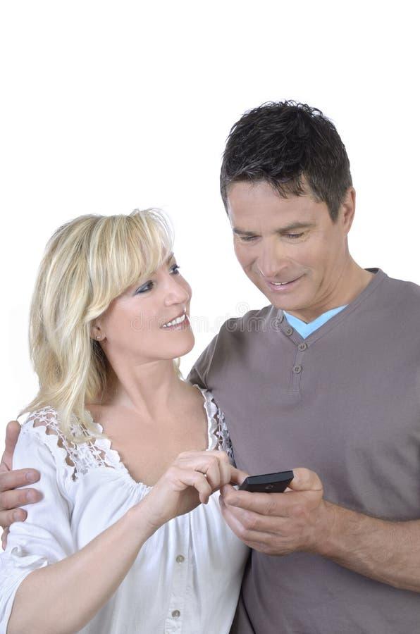 Rijp paar die pret met smartphone hebben stock afbeelding