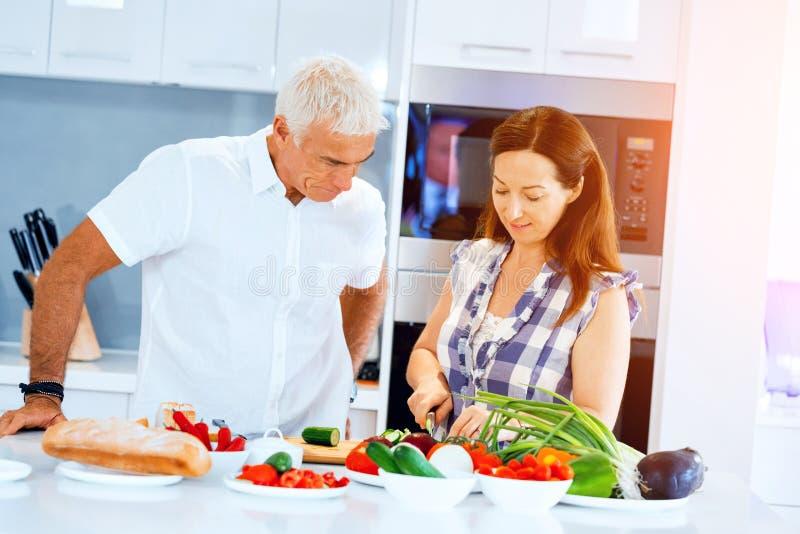 Rijp paar die thuis koken stock afbeelding
